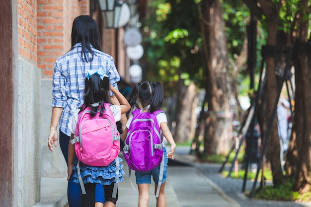 Азиатская девушка зрачка матери и дочери при рюкзак держа руку и идя в школу совместно