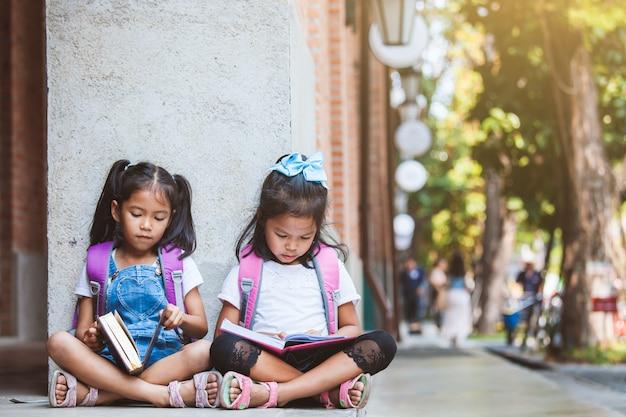 Две милые азиатские ученицы читают книгу вместе в школе с удовольствием и счастьем