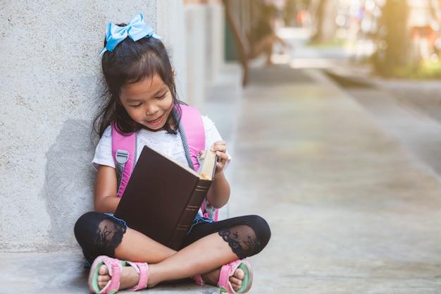 幸せな学校で本を読んでかわいいアジア生徒女の子