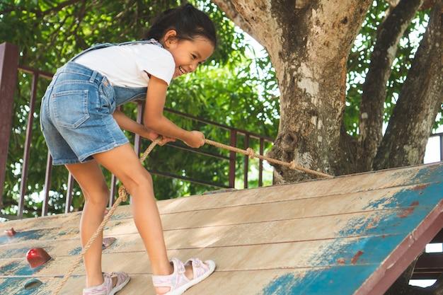 アジアの子供のかわいい女の子が遊び場でロープで木製の壁を登っています。