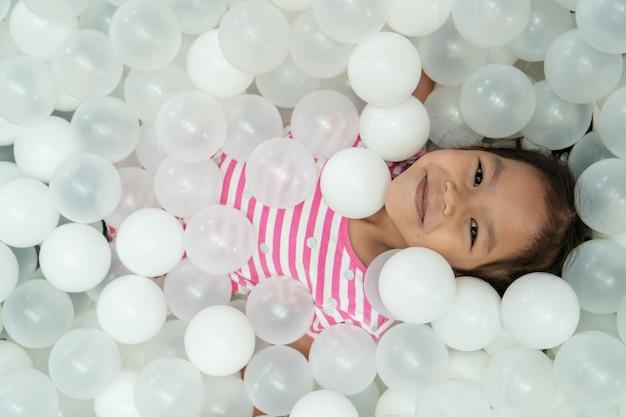 遊び場で白いプラスチック製のボールで遊ぶことを楽しんで幸せかわいいアジア子供女の子