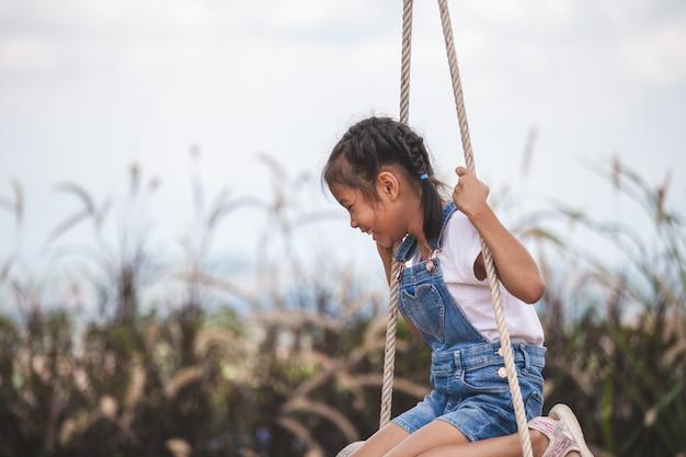 Счастливая азиатская девушка ребенка имея потеху сыграть на деревянных качелях в спортивной площадке