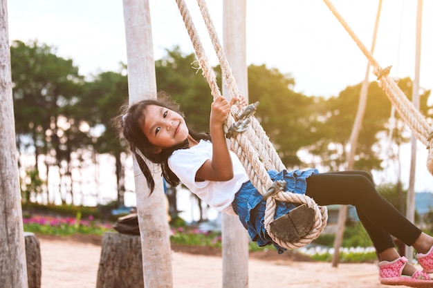 Счастливая азиатская девушка ребенка имея потеху сыграть на деревянных качелях в спортивной площадке с красивейшей природой