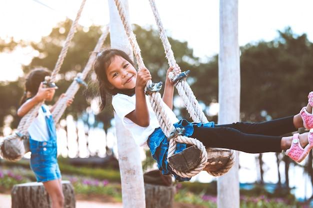 Счастливая азиатская девушка ребенка имея потеху сыграть на деревянных качелях с ее сестрой в спортивной площадке