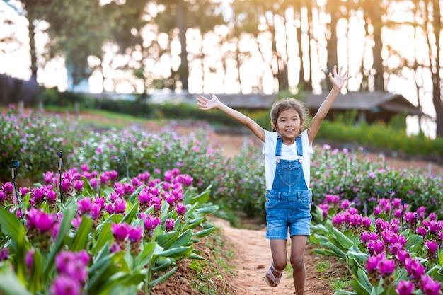 かわいいアジアの子供の女の子は彼らの腕を上げるし、花の庭で走る