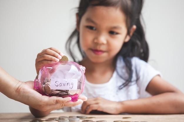 Родительская рука держит копилку и милая азиатская девочка ребенка положить деньги в копилку