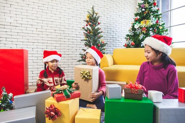 ギフト用の箱と飾ることのためのかわいいアジアの子女の子をクリスマスフェスティバルで祝う