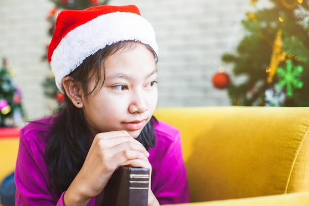 Азиатская девушка подростка делая руки сложенные в молитве для того чтобы пожелать в праздновании рождества