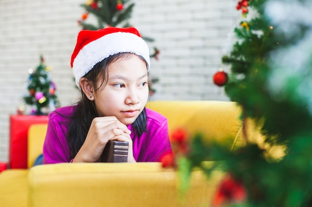 クリスマスのお祝いに希望する祈りで折り畳まれた手を作るアジアのティーンエイジャーの女の子