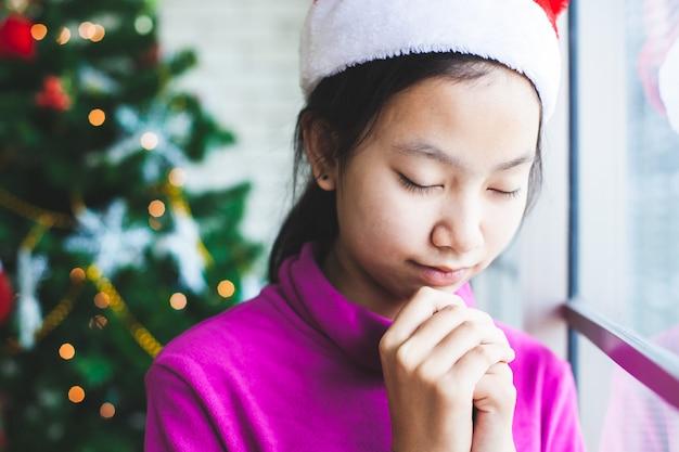 アジアのティーンエイジャーの女の子は目を閉じて、クリスマスのお祝いに願いを込めて手を組んで