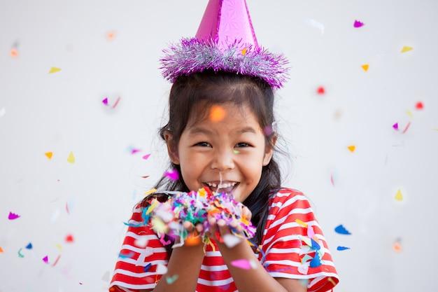 彼女のパーティーで祝うためにカラフルな紙吹雪とかわいいアジアの子女の子