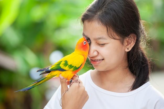 Красивые птицы попугая стоя на руке женщины. азиатская девушка-подросток играет со своей птицей-попугаем
