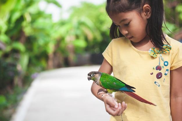 子供の手の上に立って美しい小さなオウム鳥。アジアの子供の女の子は彼女のペットのオウムの鳥と遊ぶ