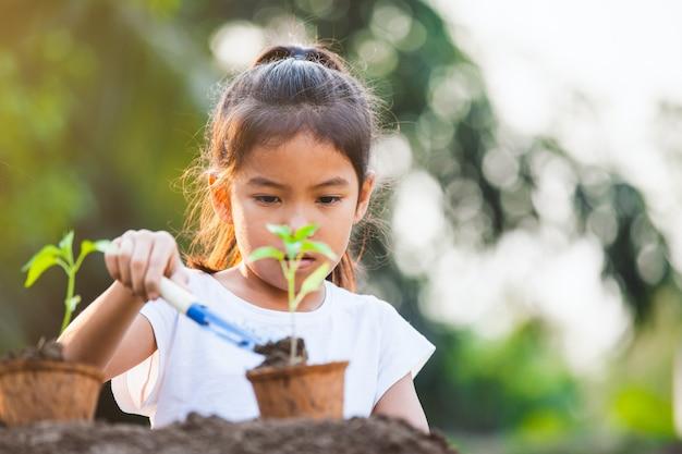 Милая азиатская девушка ребенка засаживая молодое дерево в рециркулирует баки волокна в саде с потехой
