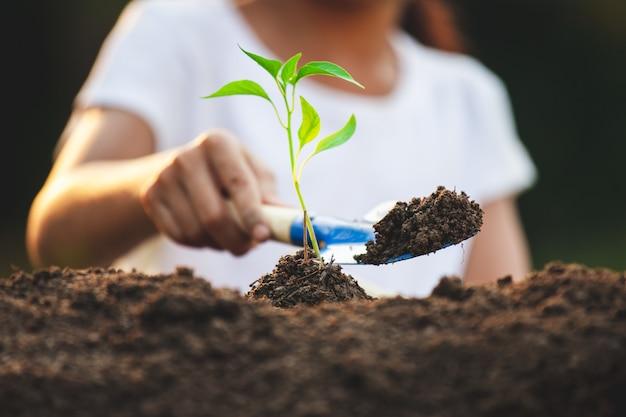 Милая азиатская девушка ребенка засаживая молодое дерево в черной почве в саде