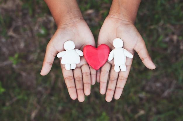 Пластилиновая глина пара с сердцем на руке ребенка. счастливый любовник и валентина концепции.