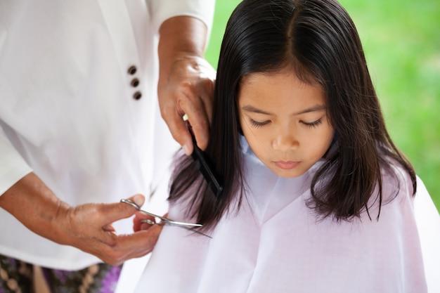 Милая азиатская девушка ребенка получая стрижку бабушкой дома
