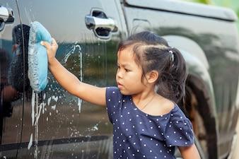 かわいいアジアの少女の洗車