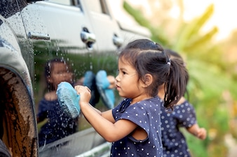 かわいいアジアの少女は、ヴィンテージ色調で車を洗う