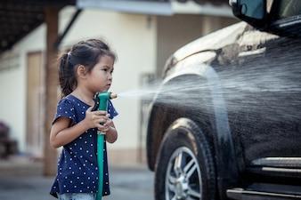 親が車を洗うのを助けるかわいいアジアの少女