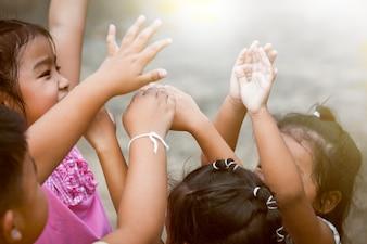 Дети поднимают руки и играют вместе в парке в старинном цветовом тоне