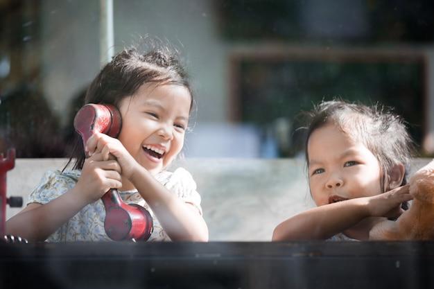 ビンテージの色調のカフェで遊んで話す幸せなアジアの少女