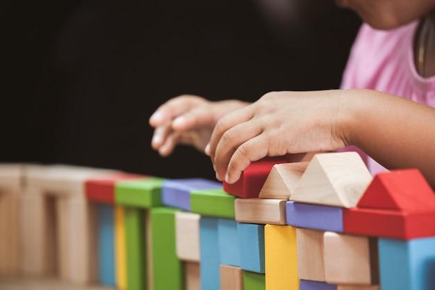 カラフルな木製ブロックで遊んでいる子供の手にビンテージ色調で焦点を当てる