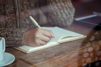 雨の日にカフェでノートを書く女性。ヴィンテージ色調