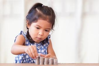 かわいいアジアの少女は、コインのスタックを作る。