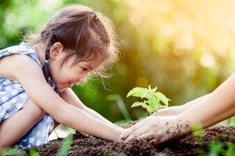 アジアの少女と親、一緒に若木を植えて