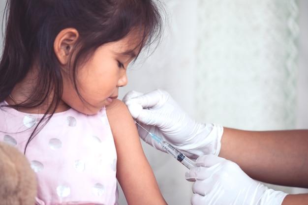 Доктор, вводящий вакцинацию в руки азиатской маленькой девочки, здоровая и медицинская концепция