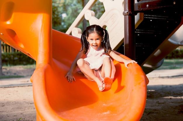 夏の時間に遊び場でスライダーをプレイする楽しみを持つかわいいアジアの子供の女の子