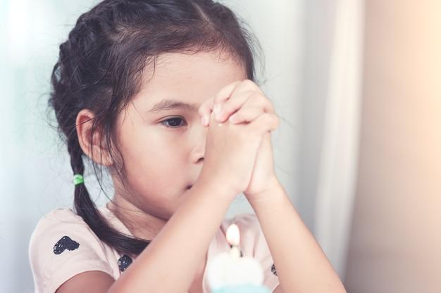 かわいいアジアの小さな子供の女の子は、ヴィンテージの色調のパーティーで彼女の誕生日のために良いものを願って折り畳まれた手を作る
