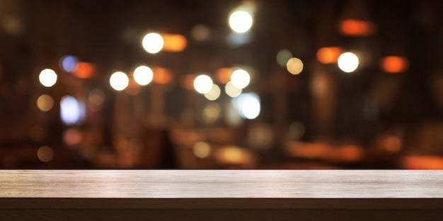 空の木製テーブルの上にコーヒーショップやレストランのインテリアの背景をぼかし