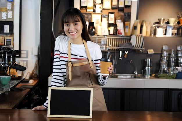 コーヒーショップでカウンターでコーヒーのカップを握っているアジアのバーリス笑顔