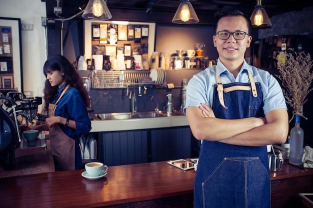 コーヒーショップでカウンターを横断した腕を持つアジアのバリスタの肖像