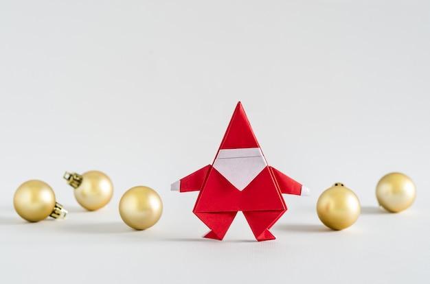 サンタクロースのペーパークラフトと白い背景の黄金のボール。