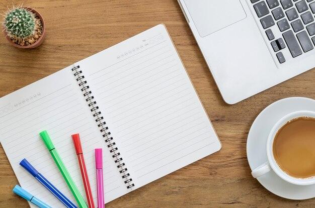 ノートパソコン、コンピュータのラップトップ、カラーペン、サボテン、コーヒーのカップ付きの木製の机のテーブル。コピースペースを持つトップビュー。