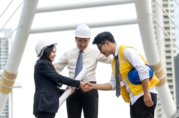 ビジネスハンドシェイク。建築家の握手とビジネスの人々のコンセプト。