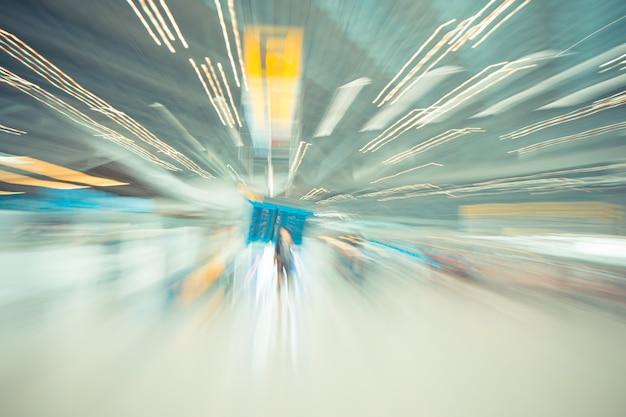 Размытым фоном движения: путешественник в аэропорту терминала заезд размытия фон с боке света