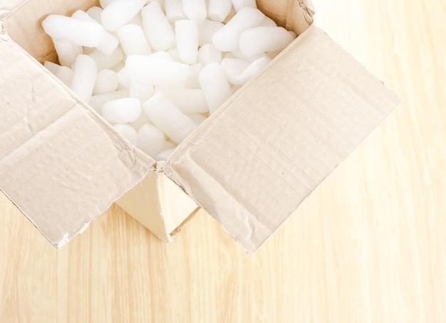 白い泡の入った開いた詰め物の入った茶色の箱は、木製のテーブル