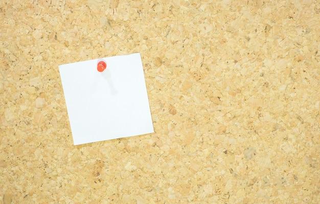 コルクボードに赤い押されたメモ帳