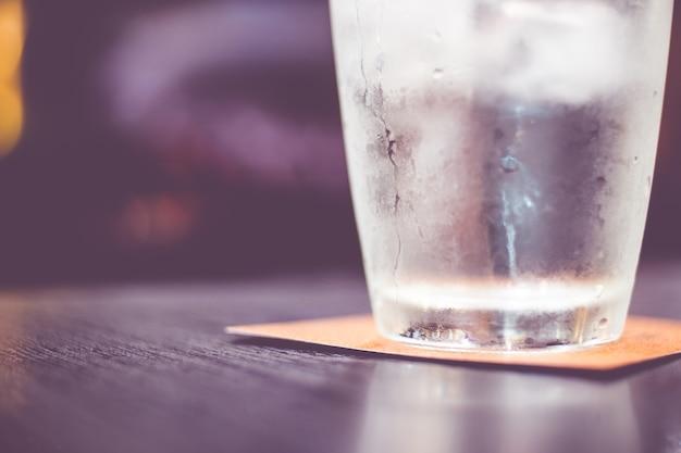 ヴィンテージフィルター:レストランの木製テーブルに水の冷たいガラス