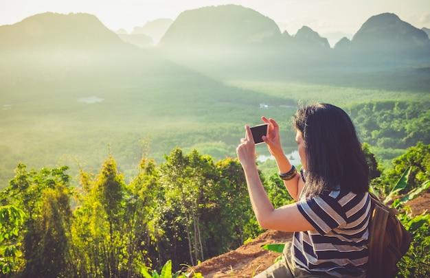 若い旅行者の女性のバックパッカー携帯電話を使用して山の頂上で日の出の美しい写真を撮る