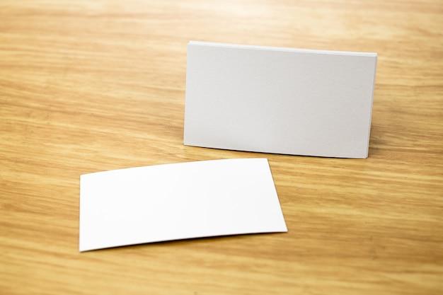 空の名刺は、光の木製のテーブル上で模倣し、ビジネスコーポレートアイデンティティ