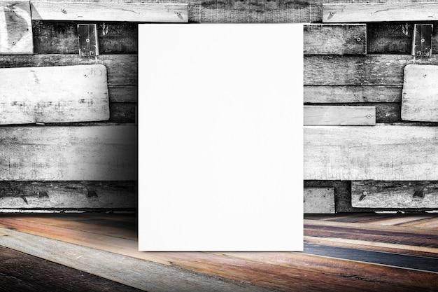 Пустой плакат, прислоненный к деревянной стене доски и диагональному деревянному полу