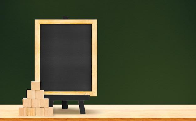 暗い緑の背景に木製のテーブルに黒板と木製のキューブ