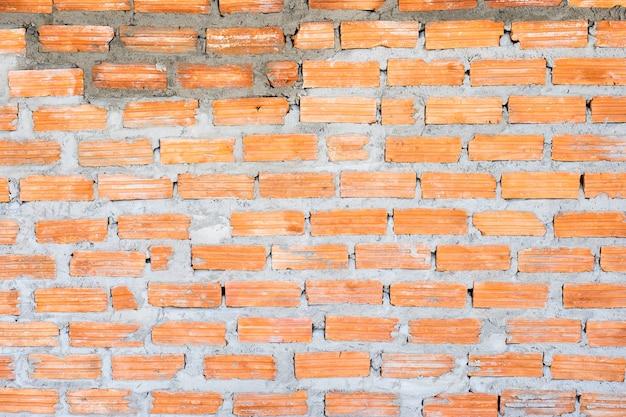 セメント壁のテクスチャの背景とオレンジ色のレンガ。