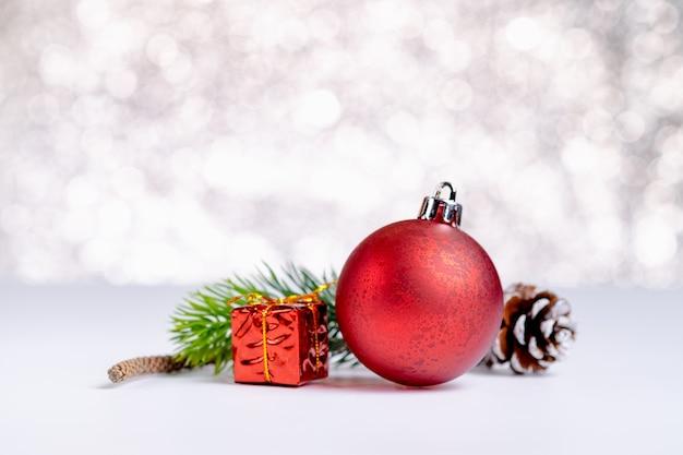 赤いクリスマス光沢のあるボールと輝くボケの白いテーブルにギフトボックスのグループを閉じます