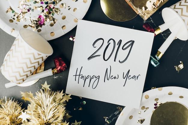 パーティーカップ付きの大理石のテーブルのグリーティングカードに新年あけましておめでとうございます